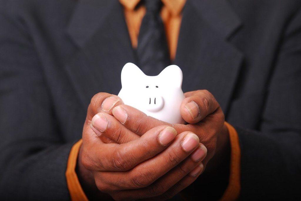 白い豚の貯金箱を抱える男性