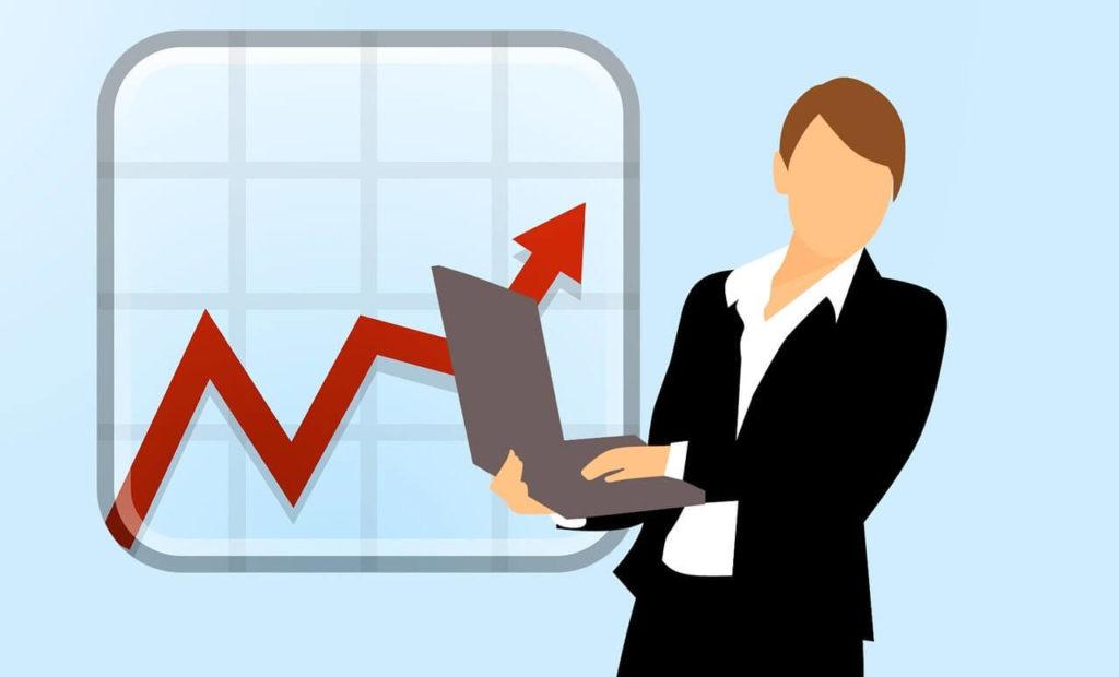 ノートPCを持つスーツの女性とチャート