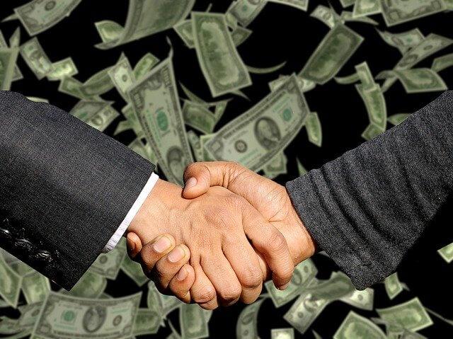 お金の背景の前で握手をする男性