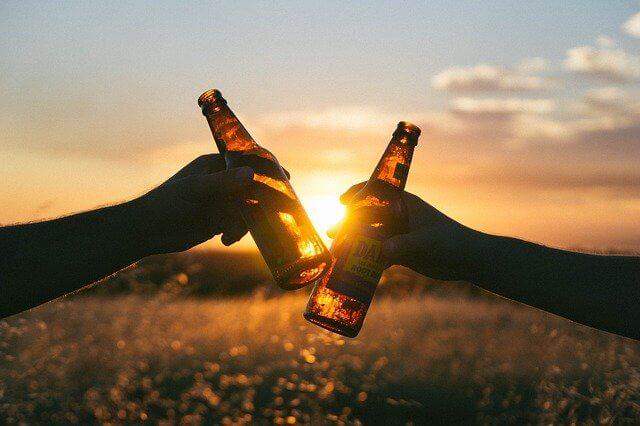 夕日の前で乾杯する2人