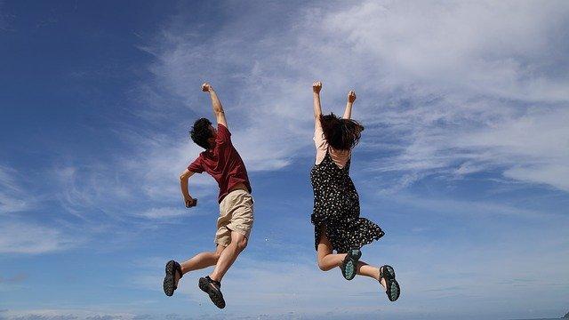 青空の下でジャンプする男女